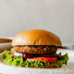 a lentil burger on a bun with lettuce, tomato, and onion