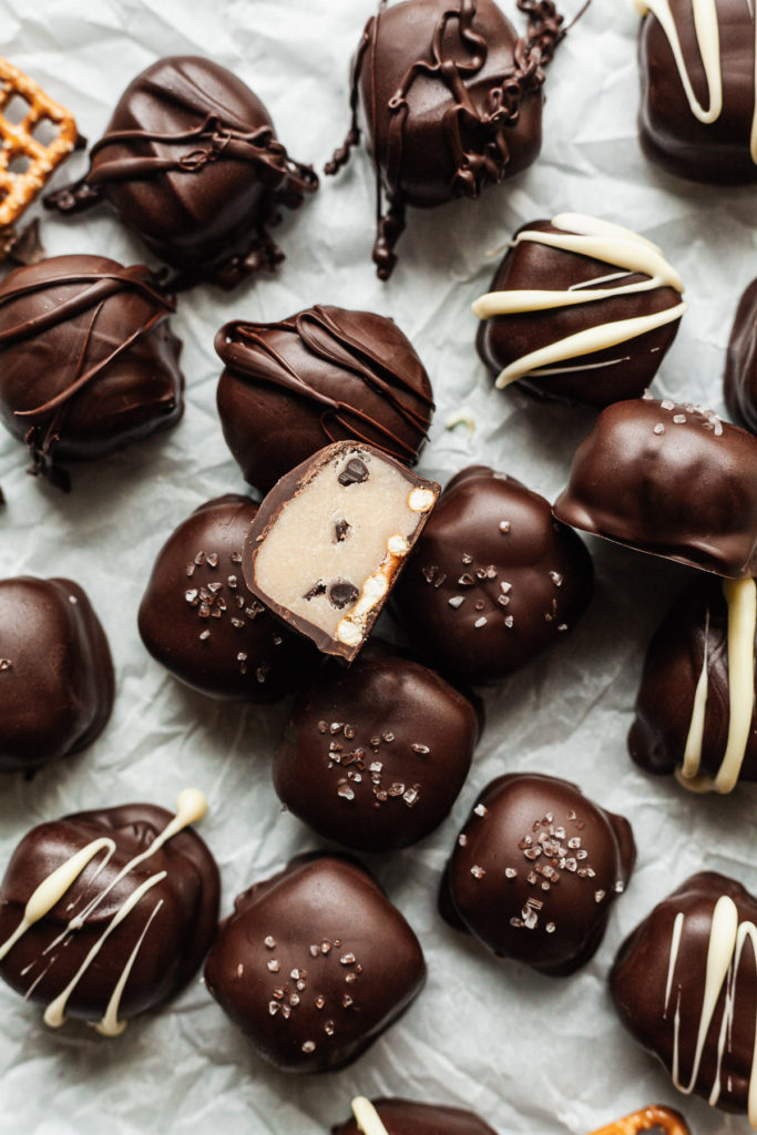 pretzel cookie dough truffles on white parchment paper with one cut in half