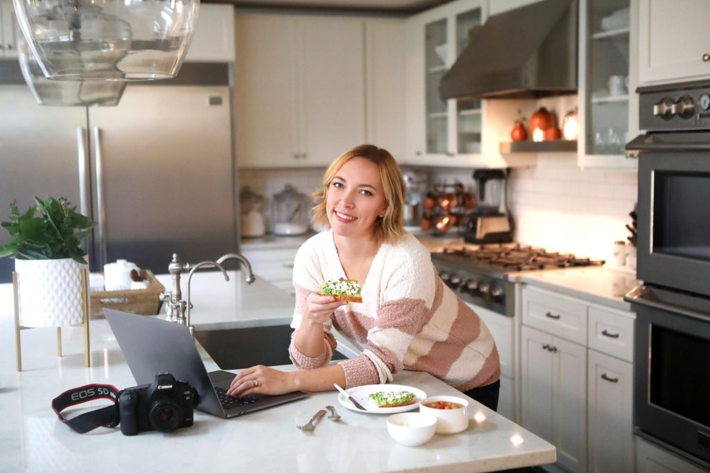 image of Lindsay Moe in a kitchen with computer and avocado toast