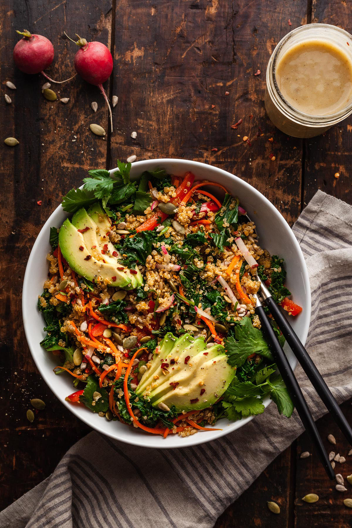 a bowl of warm kale and quinoa salad on a wood table