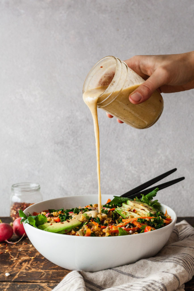 a hand pouring creamy tahini dressing on a kale salad
