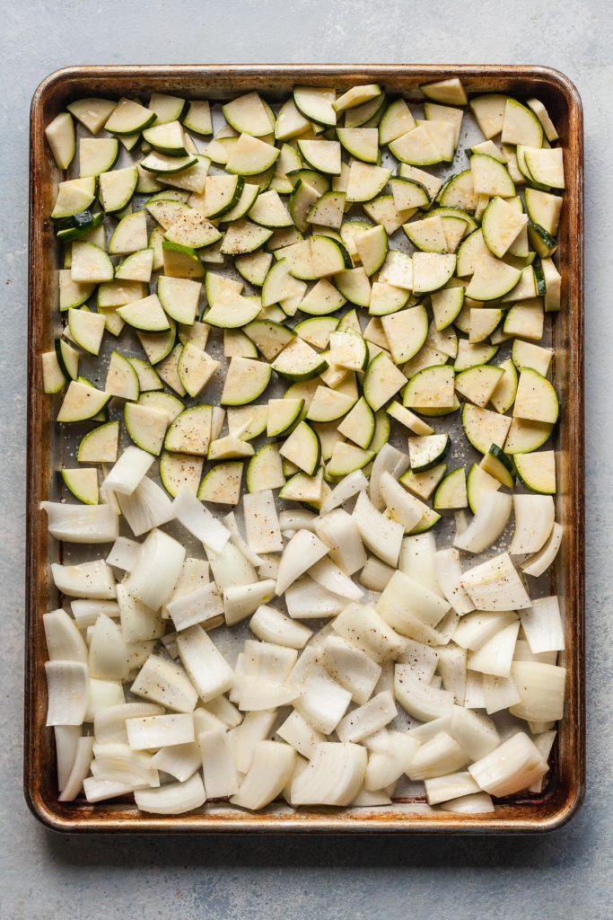 onions and zucchini cut on a baking sheet before cooking