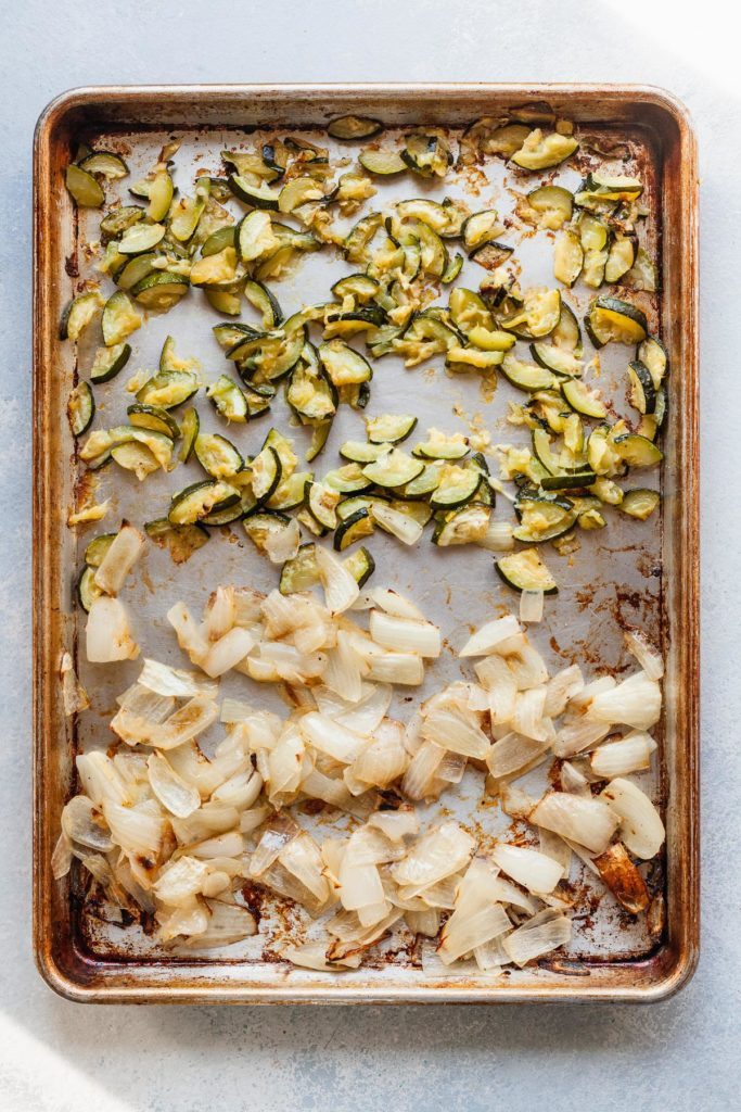 onions and zucchini cut on a baking sheet after cooking