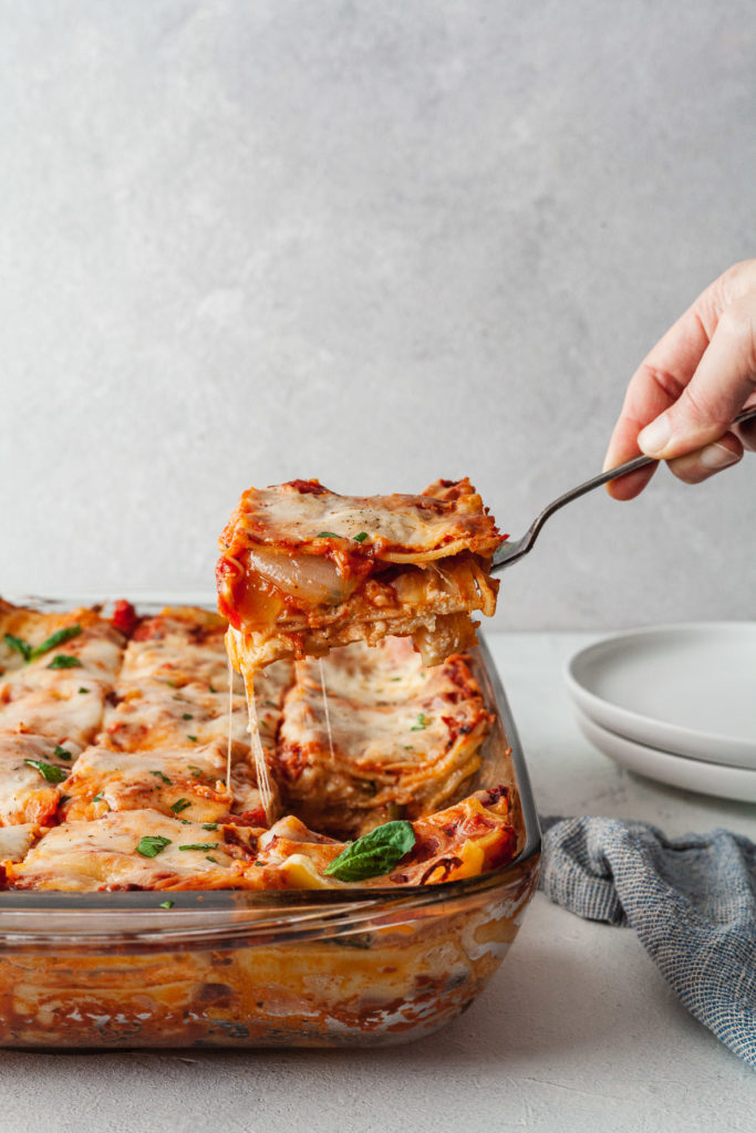 a slice of cheesy vegetarian lasagna being scooped out of a dish