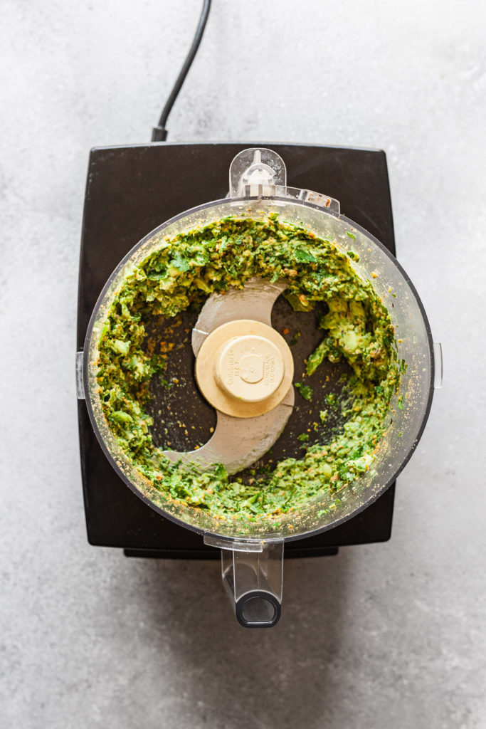 green avocado sauce in a food processor after chopping