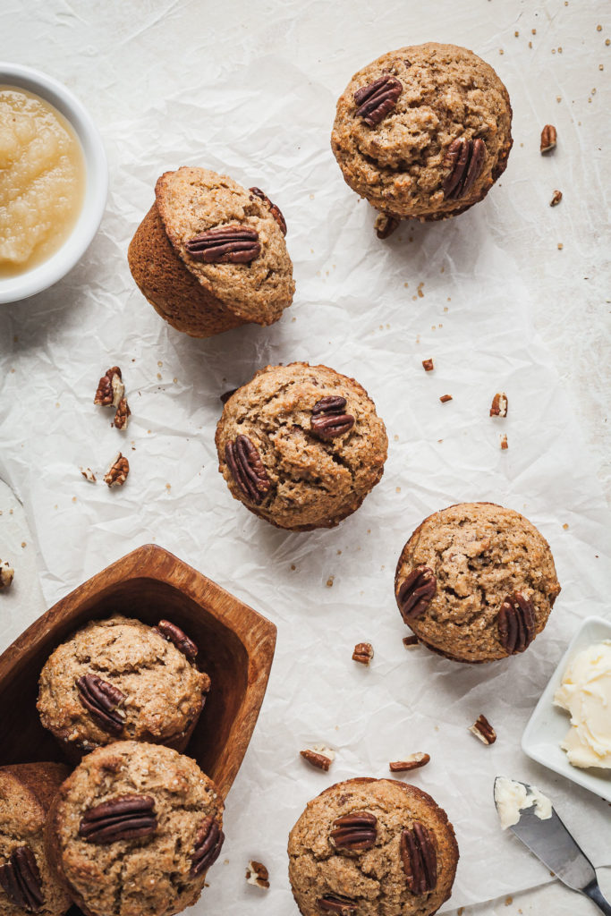 apple spice muffins on white parchment with a bowl of applesauce