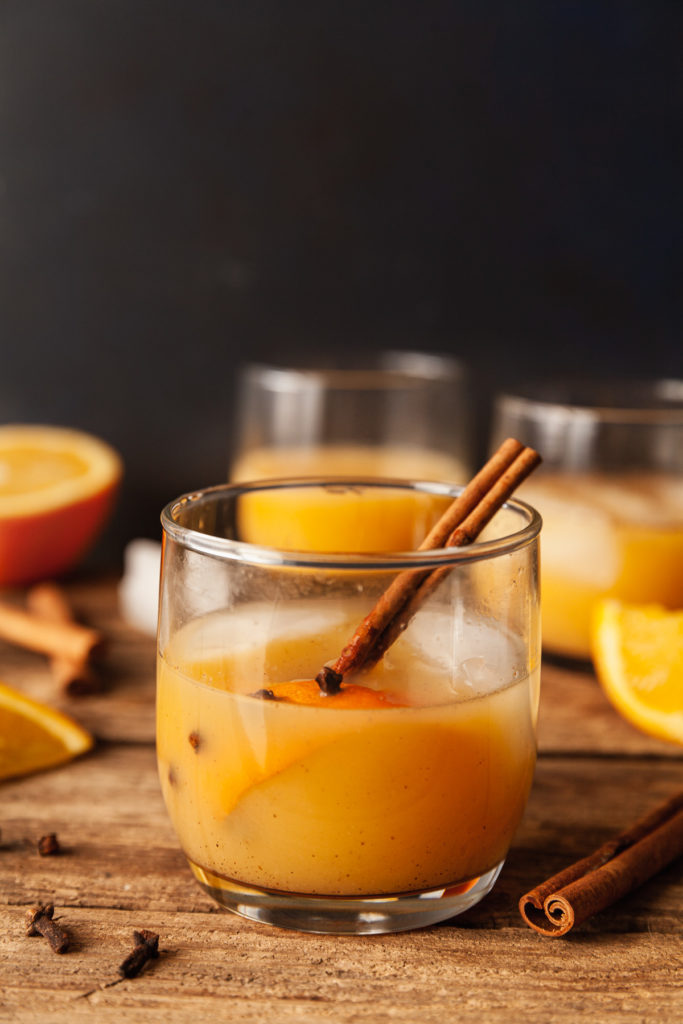 a spiced vodka orange juice on a wood table