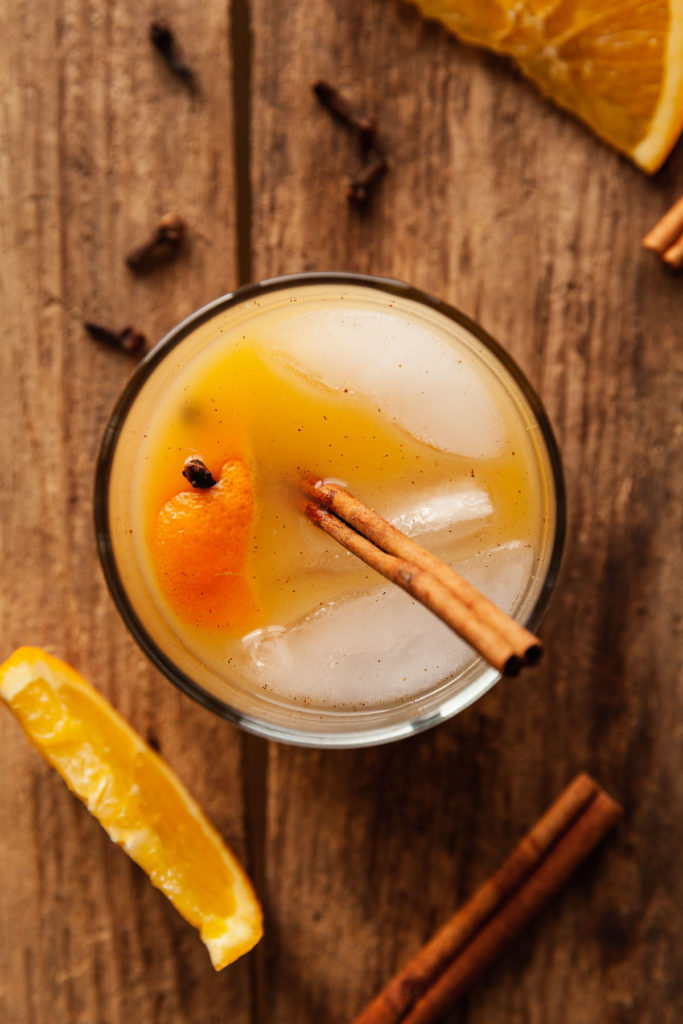 overhead photo of a screwdriver cocktail with cinnamon and clove
