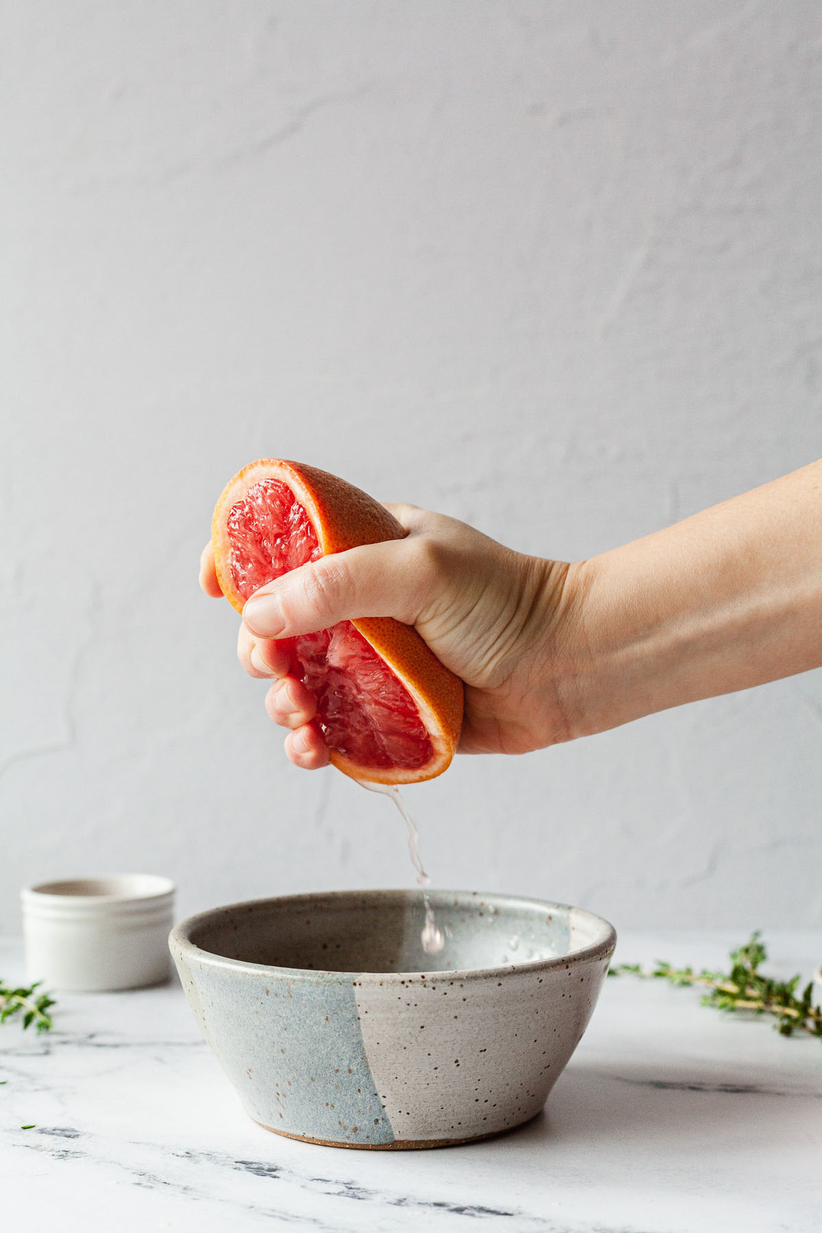 a hand squeezing juice from a grapefruit into a small bowl