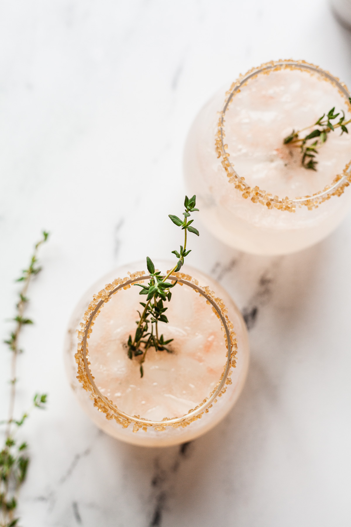 overhead photo of two grapefruit vodka drinks with fresh thyme