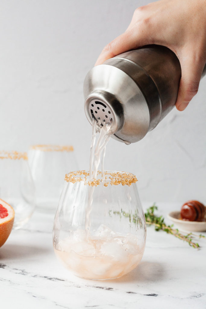 a hand pouring grapefruit juice and vodka from a shaker into a glass rimmed with sugar