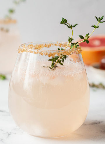 a sparkling greyhound cocktail with a sprig of thyme on a marble table