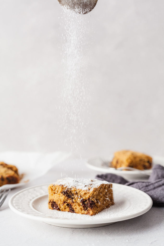 butternut squash cake being sprinkled with powdered sugar