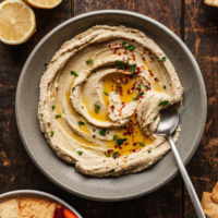 a bowl of basic hummus with a spoon