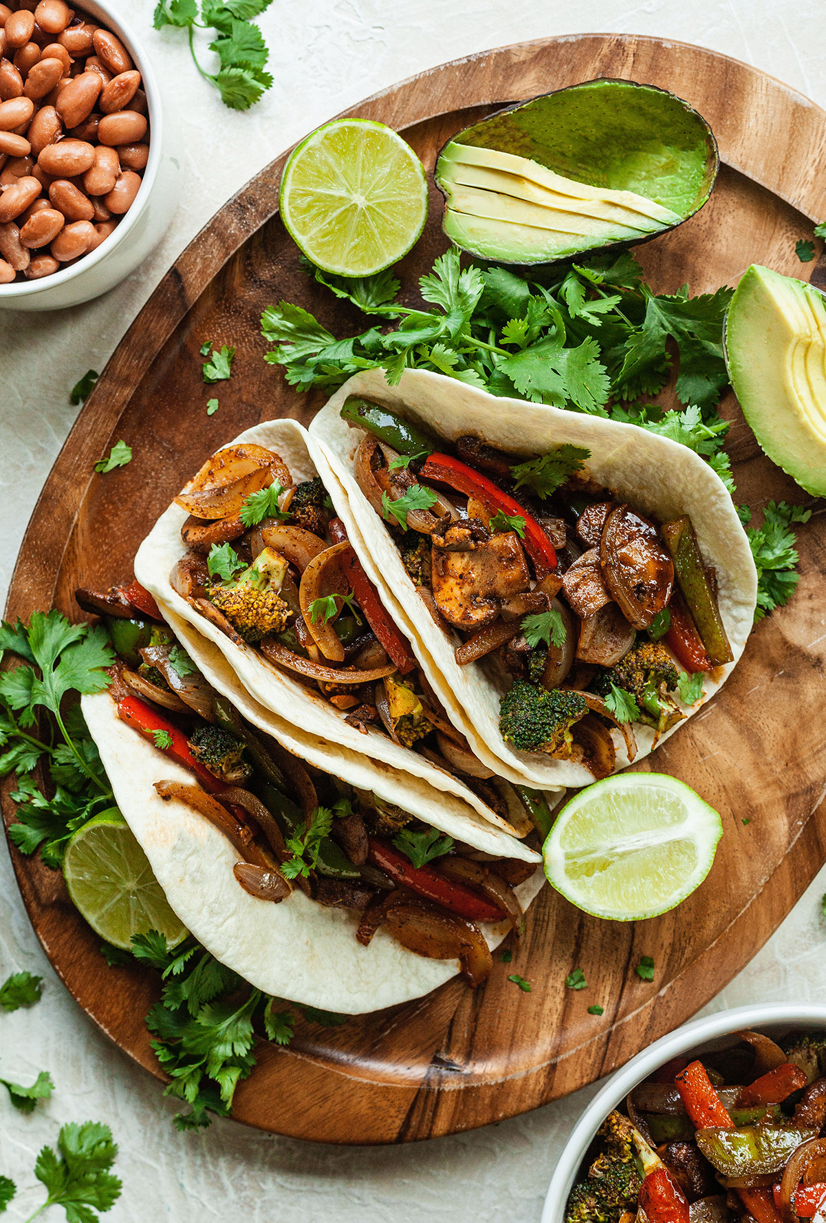 three vegan fajitas on a platter with limes, avocado, and cilantro