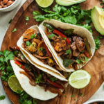 three vegan fajitas on a wood platter with limes and cilantro