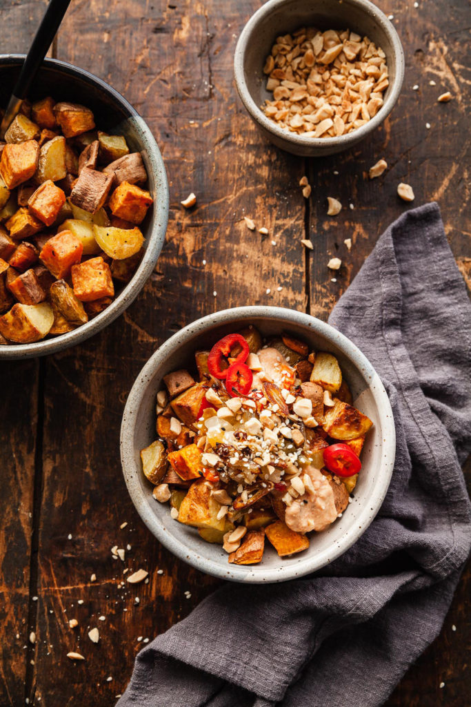 crispy potatoes in a bowl with thai tofu sauce and peanuts