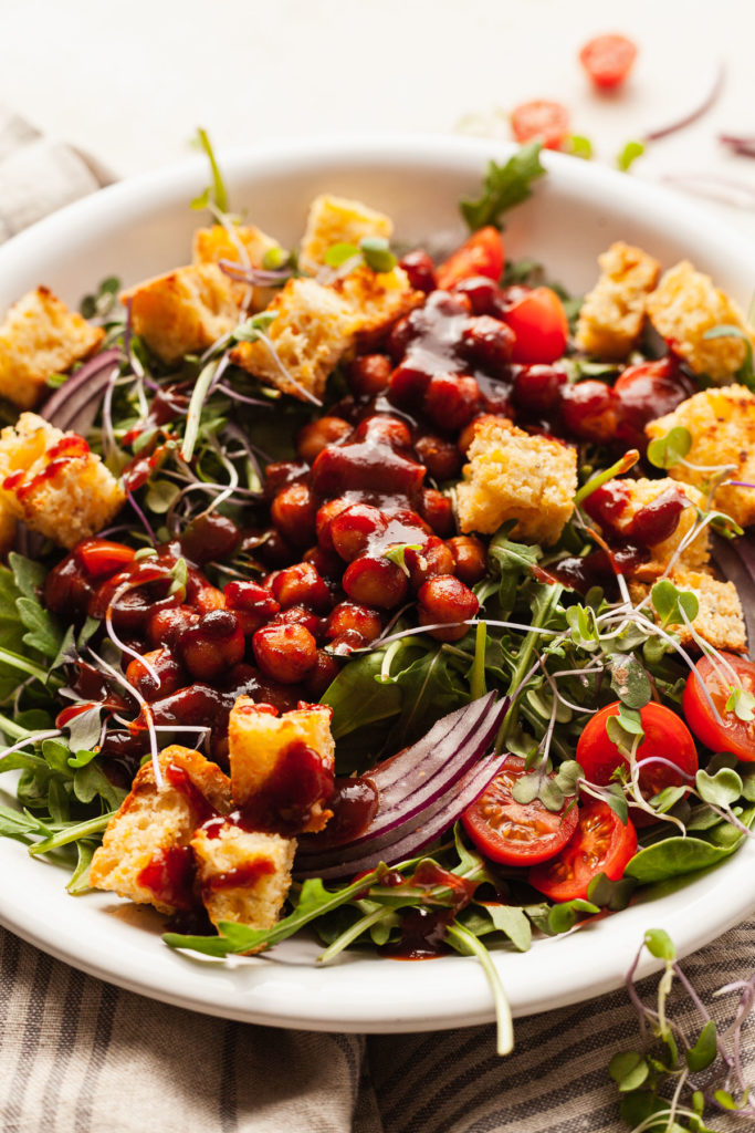 a white bowl of salad with arugula, onions, tomatoes, chickpeas, and cornbread croutons
