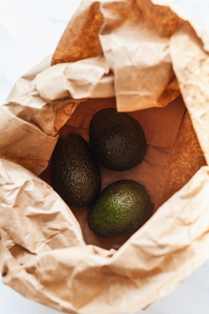 three avocados in a brown grocery bag