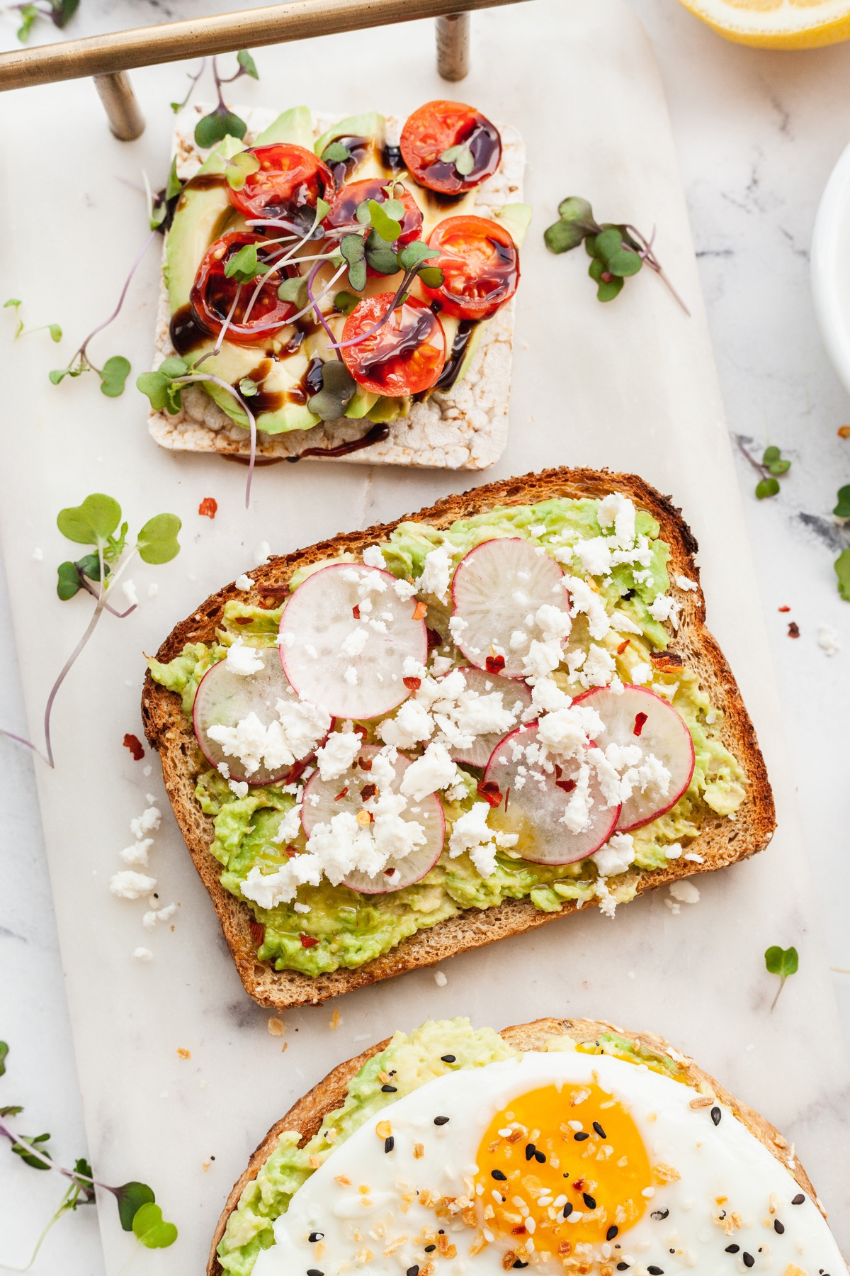 several slices of avocado toast with different toppings including sliced radishes, feta, and tomatoes