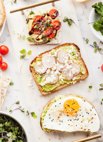 three pieces of avocado toast with different toppings