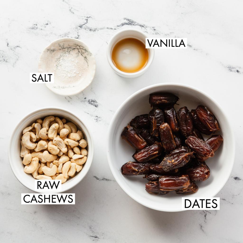 cashews, dates, vanilla and salt in white bowls