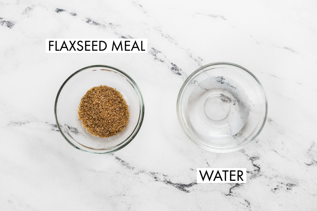 two small bowls, one with flaxseed meal and one with water