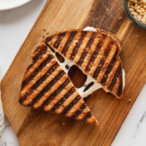 a grilled cheese sandwich cut in half on a wood cutting board