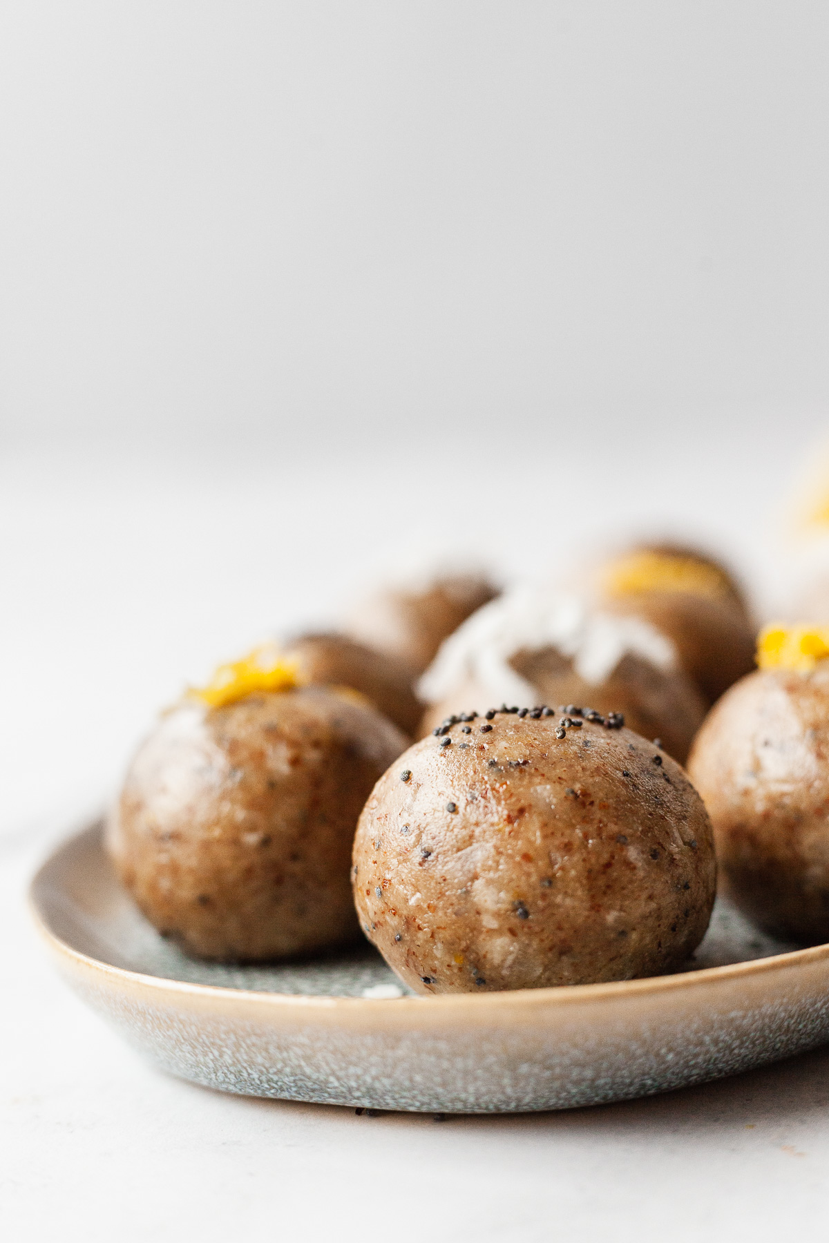 side shot of a plate of lemon poppy seed protein balls