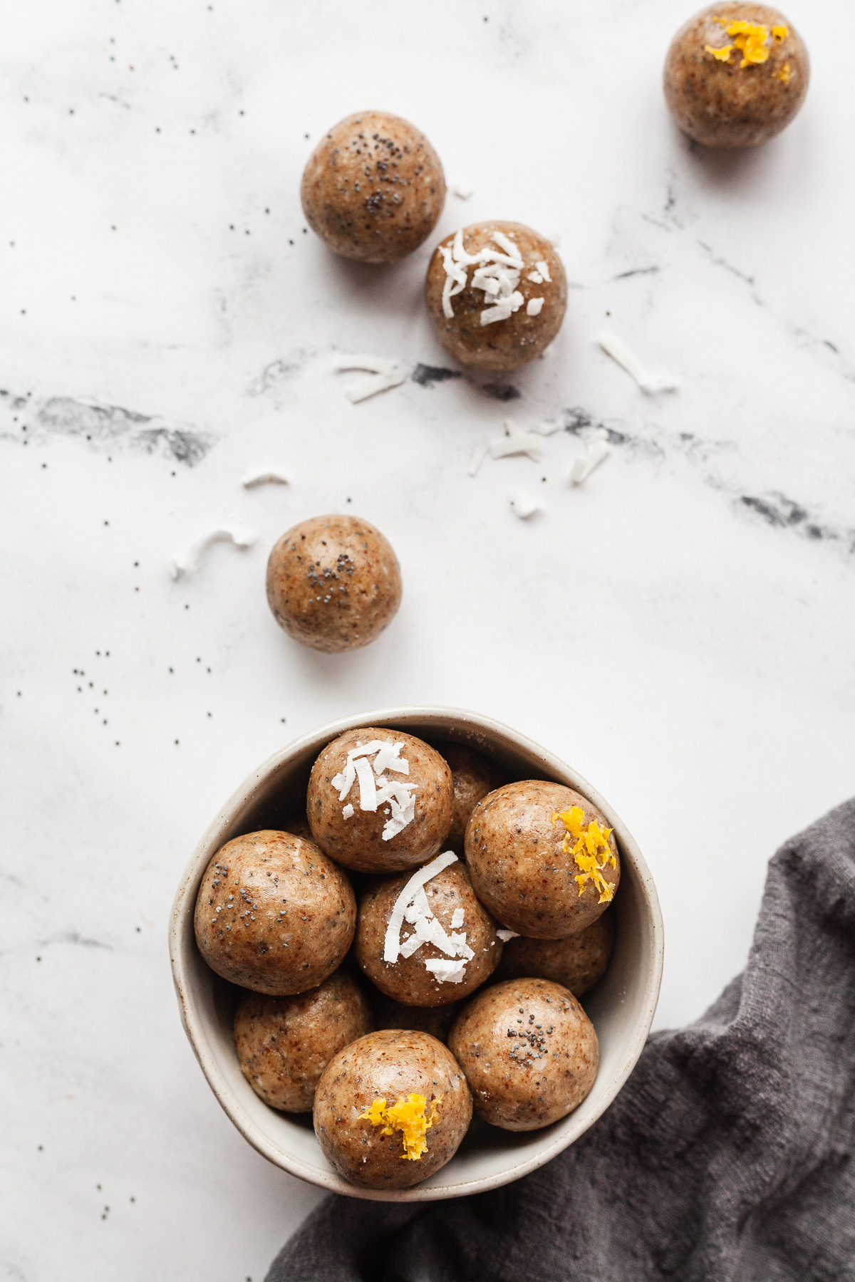 a bowl of lemon energy balls with a few on the marble table outside the bowl