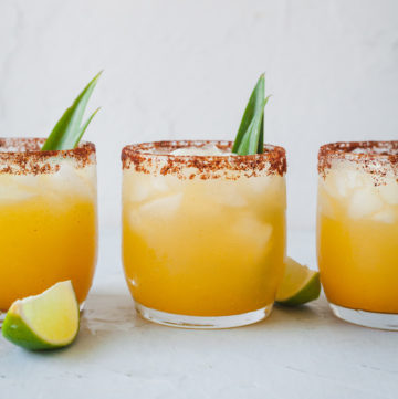 three glasses filled with pineapple margarita