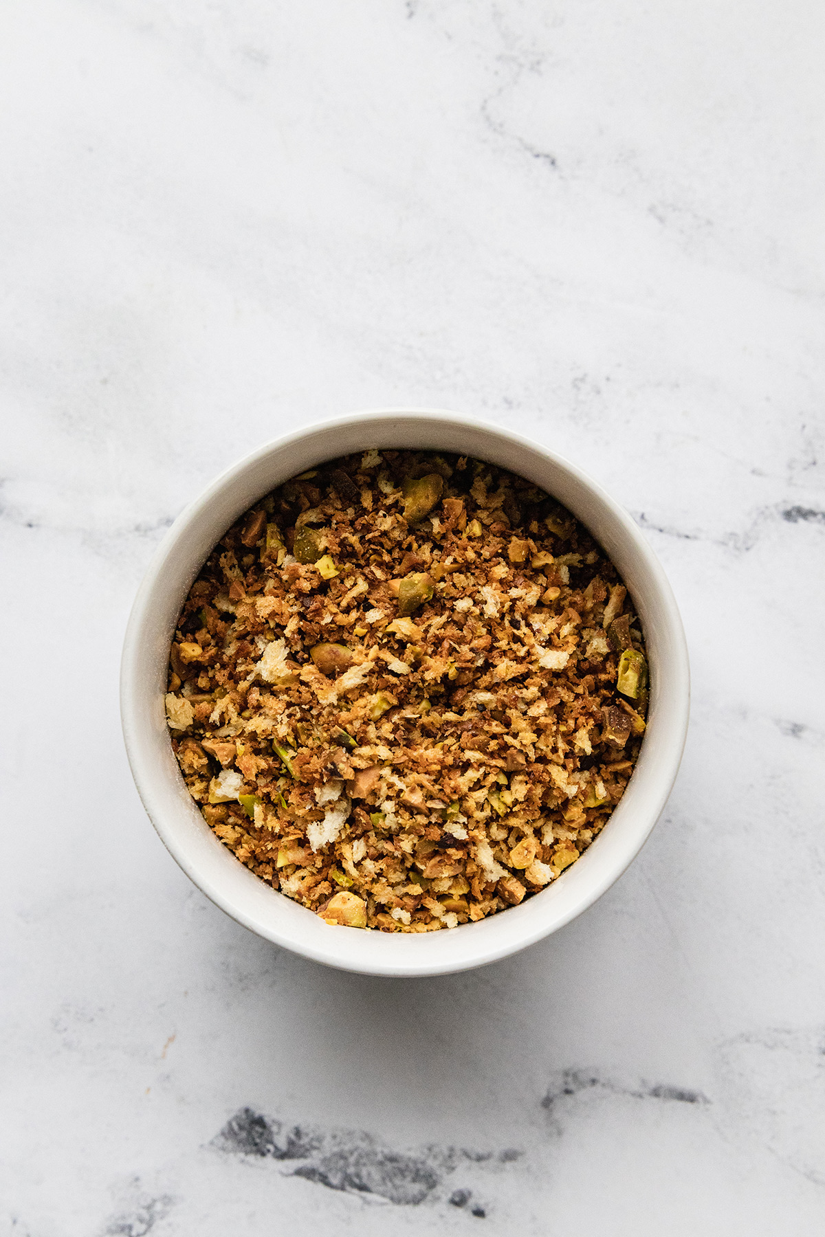image of white bowl with breadcrumbs and pistachios