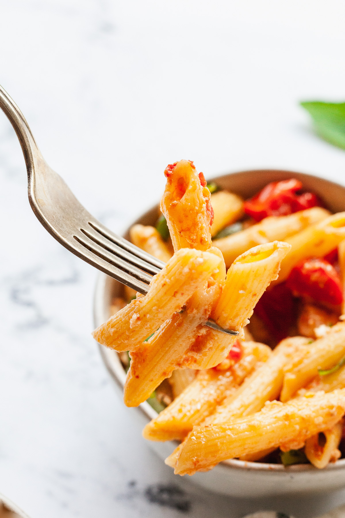 close up image of tomato and feta pasta in a bowl with some noodles on a fork