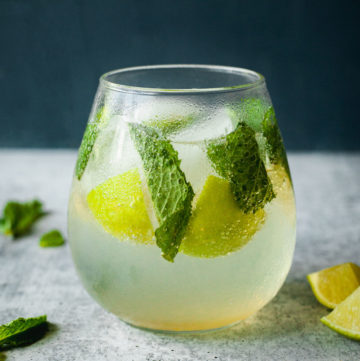 glass of a mojito mocktail from the side with mint and limes