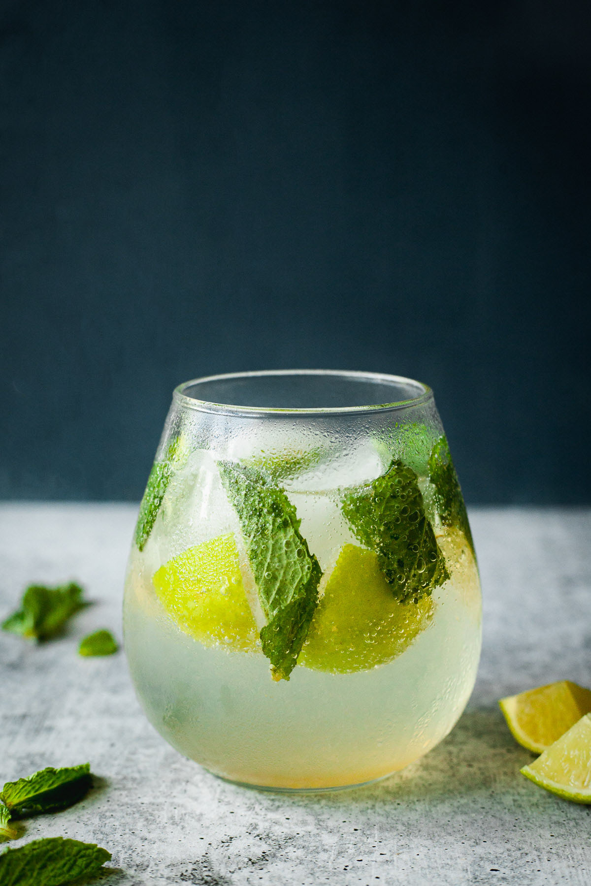 side image of a glass of mojito mocktail with mint and lime wedges with mint and limes on table