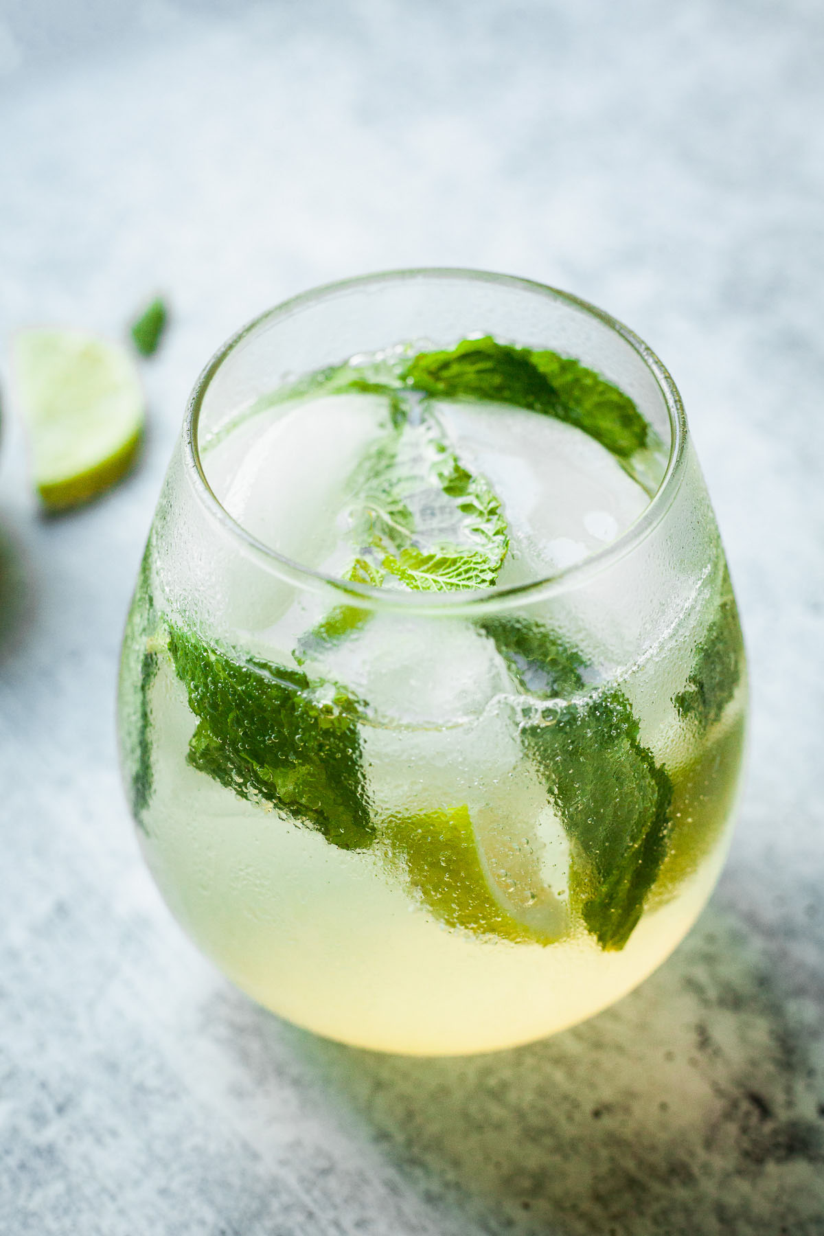 close image of top of glass with ice, mint and lime wedges