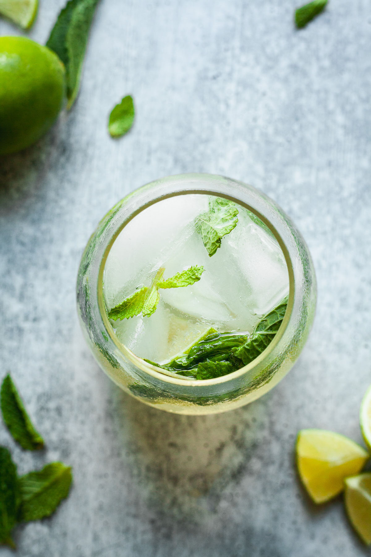 image of mojito mocktail from top of glass showing ice cubes mint and lime wedges