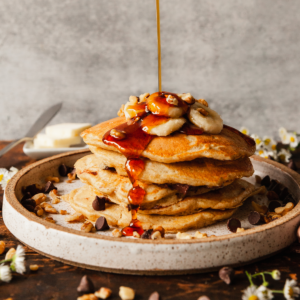 plate of banana pancakes being drizzled with syrup