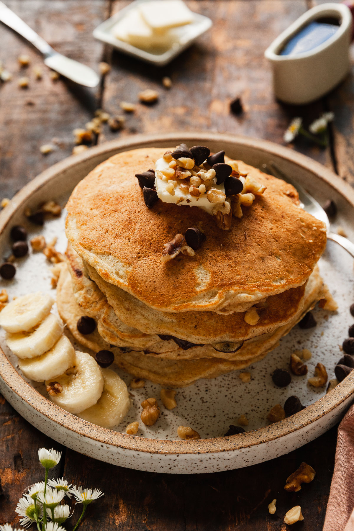 image of plate with pancakes topped with walnuts, chocolate chips and bananas
