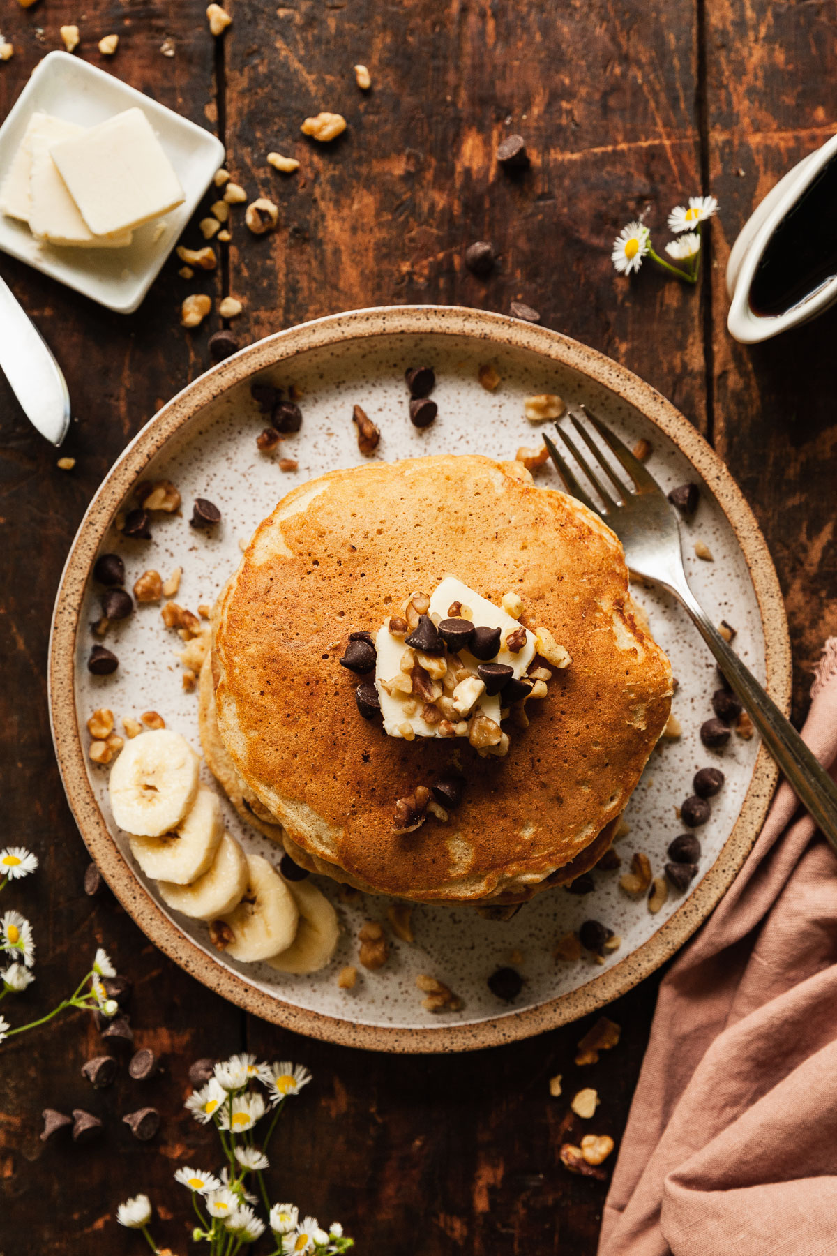 top view image of banana walnut pancakes on plate with fork on plate scattered with chocolate chips walnuts and flowers on table