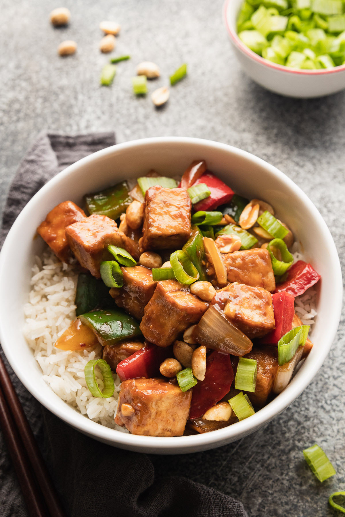image of kung pao tofu in a bowl with white rice and vegetables and a small bowl of green onions in right corner