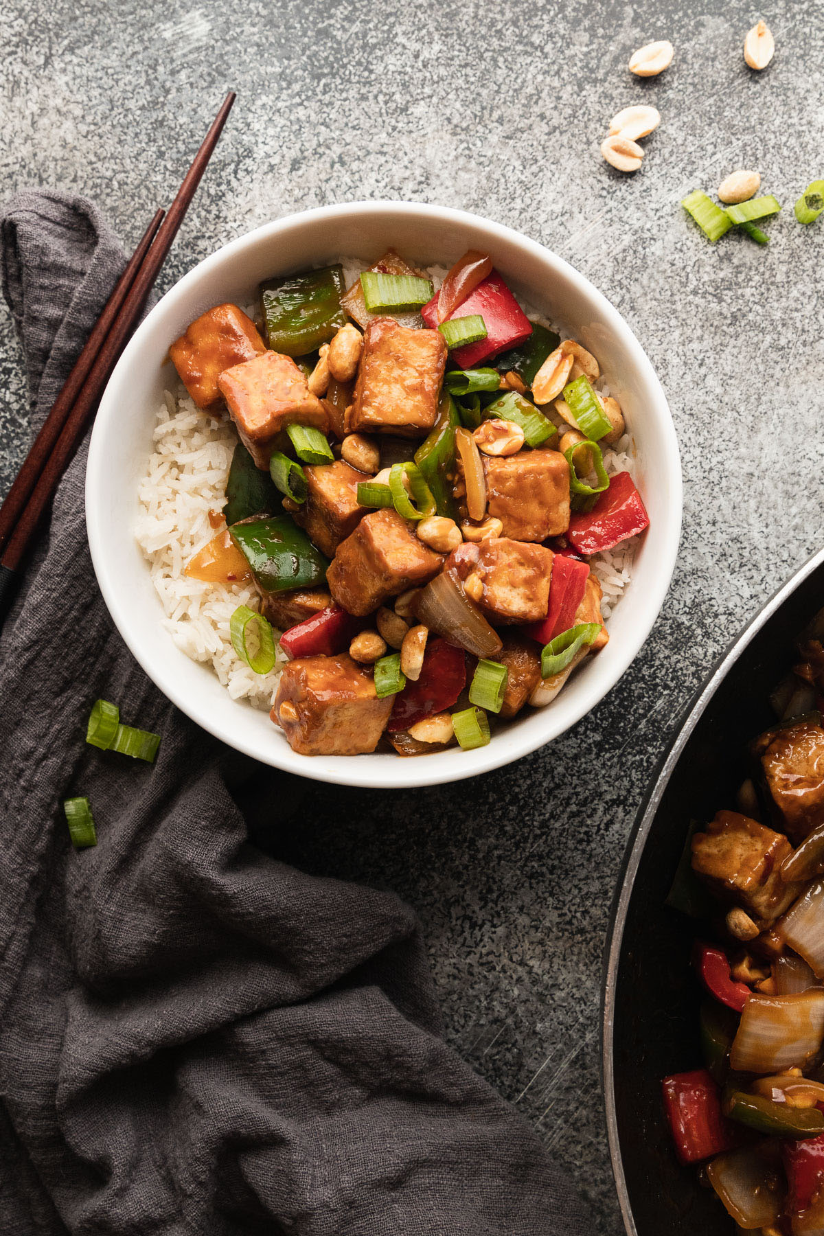 a white bowl filled with rice and kung pao tofu next to chopsticks and a dark grey napkin