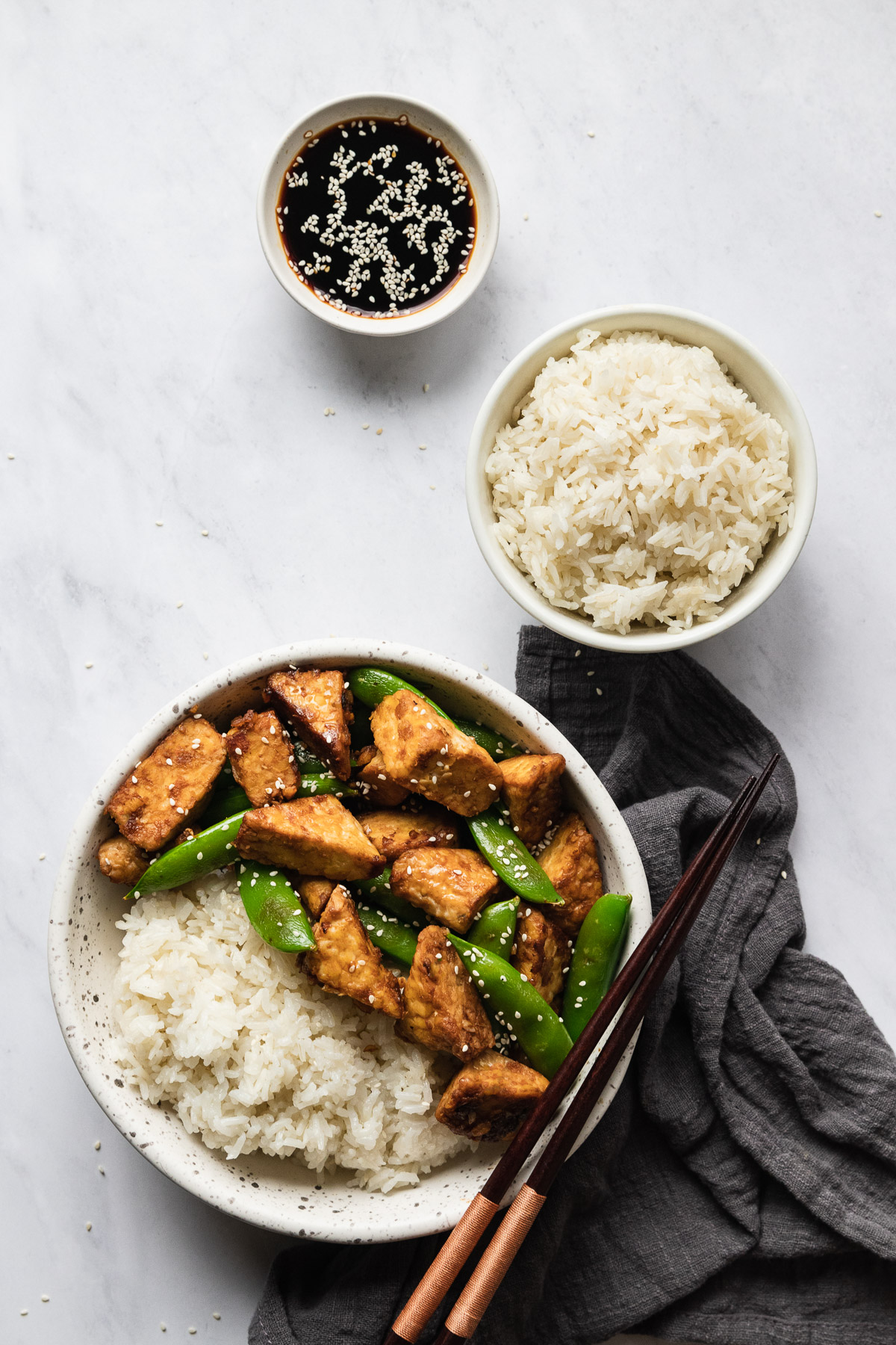 three white bowls, one with soy sauce, one with rice, and one with rice, tempeh, and snap peas