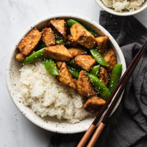 easy stir fried tempeh in a bowl with white rice and chopsticks