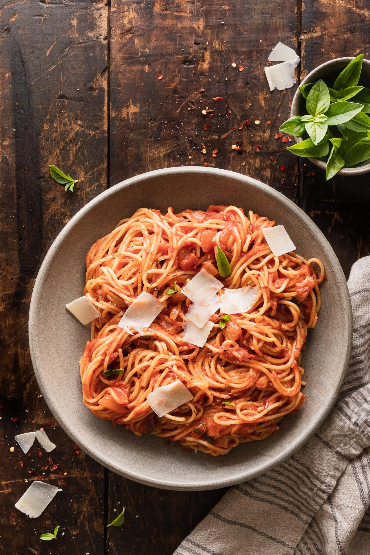 image of spaghetti arrabbiata in dish with striped towel next to dish and basil in a bowl