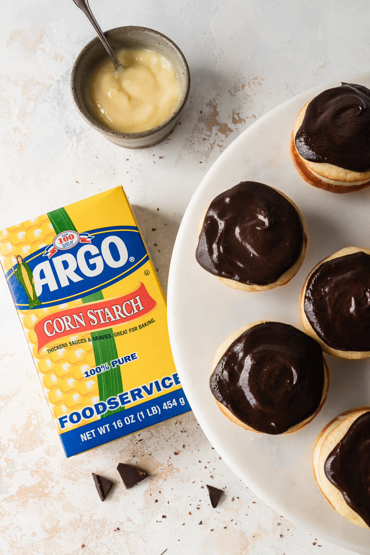 mini boston cream whoopie pies on a cake stand with a box of cornstarch