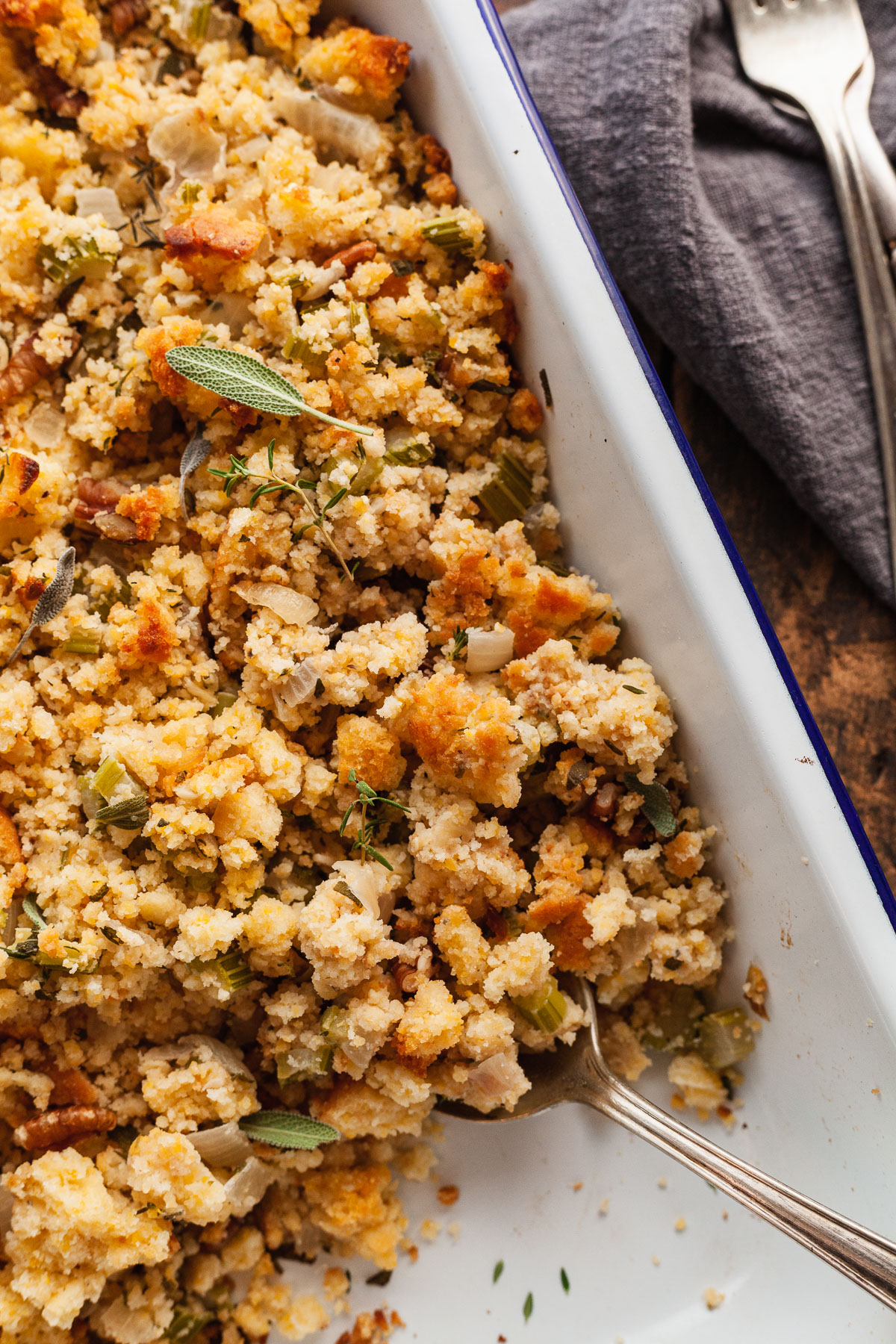 a pan of cornbread stuffing with a serving spoon