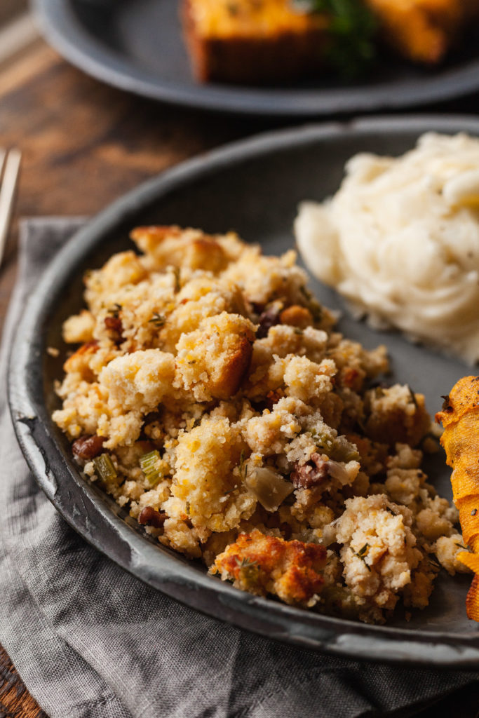 vegetarian cornbread stuffing on a blue plate with other thanksgiving foods
