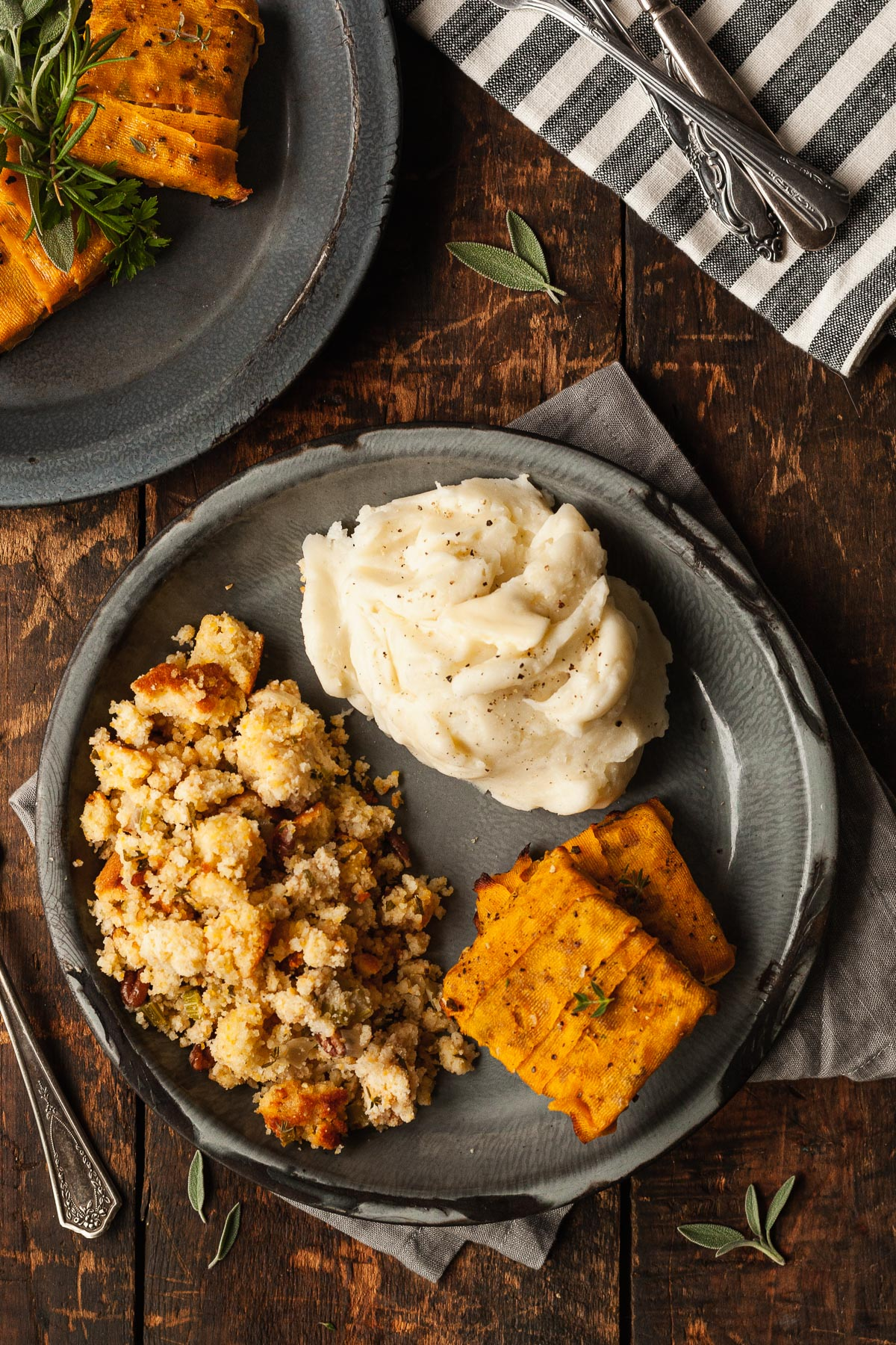 butternut squash tempeh on a plate as a vegetarian thanksgiving main dish next to mashed potatoes and stuffing