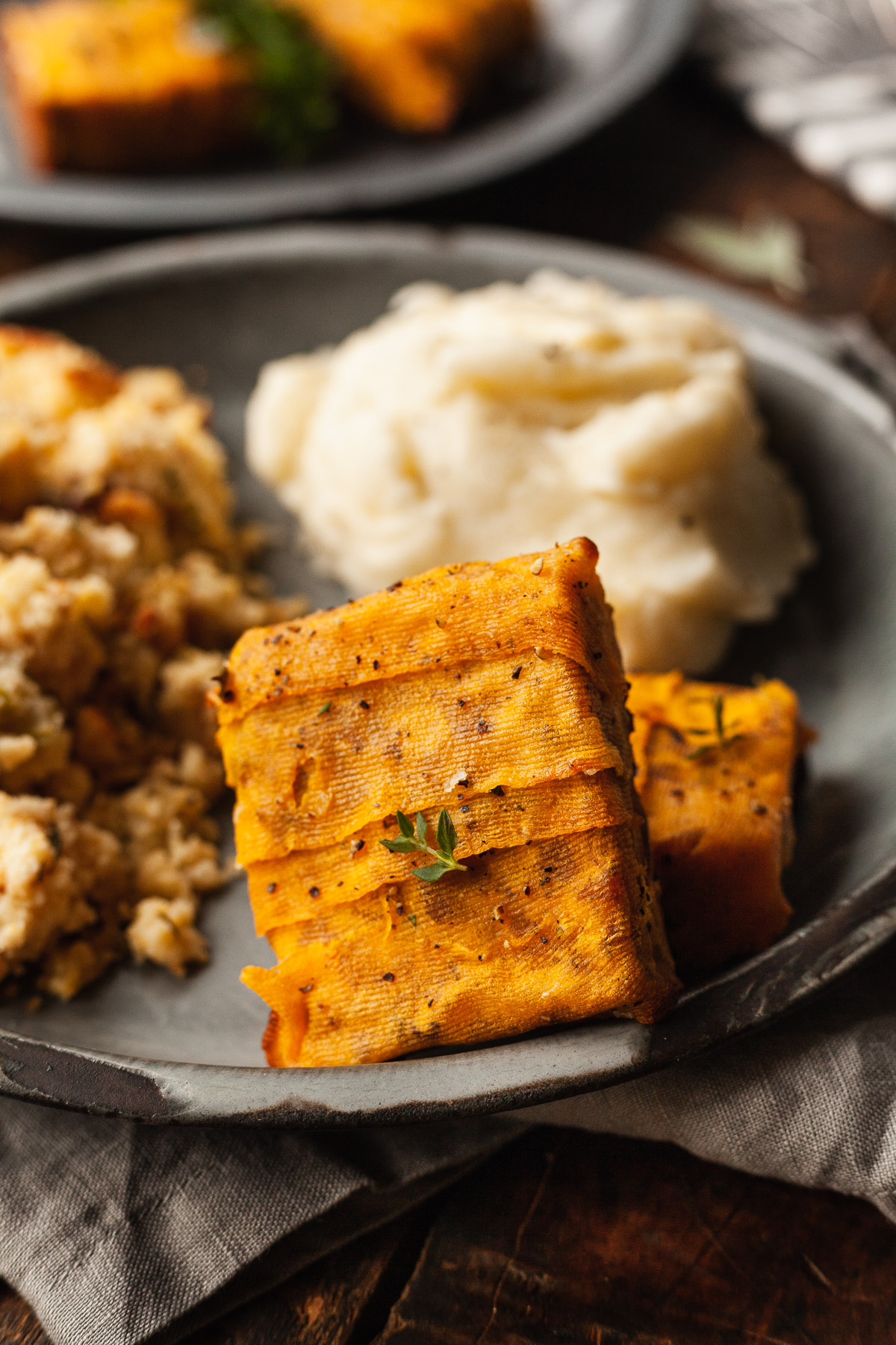 butternut squash wrapped tempeh on a plate with mashed potatoes and stuffing